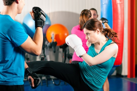female kick: Woman Boxer hitting the sandbag, her trainer is assisting
