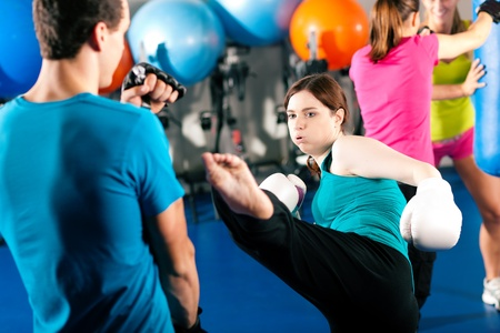 Woman Kick boxer kicking her trainer in a sparring session, in the background other boxers are hitting the sandbag