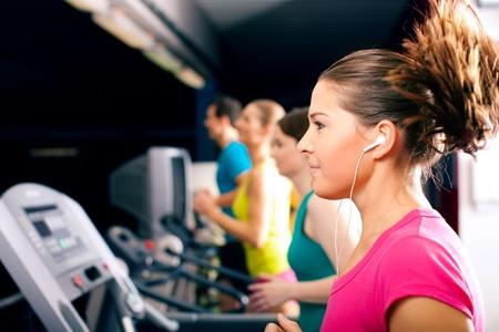 actief luisteren: Draait op loopband in gymnasium - groep voor vrouwen en mannen uitoefening te krijgen meer fitness, de vrouw in de voorkant draagt oordopjes en geniet van de muziek