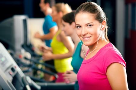 actief luisteren: Draait op loopband in gymnasium - groep van mannen en vrouwen uit te oefenen om meer fitness, de vrouw in de voorkant draagt oor dopjes en geniet van de muziek