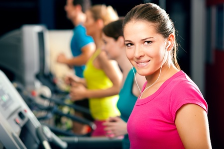 Running on treadmill in gym - group of women and men exercising to gain more fitness, the woman in front wears earplugs and enjoys music Stock Photo - 8295245