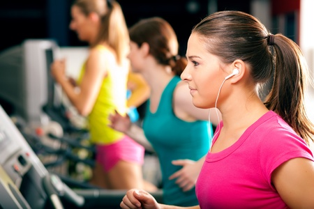 enjoys: Running on treadmill in gym - group of women and men exercising to gain more fitness, the woman in front wears earplugs and enjoys music