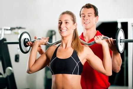 fortaleza: Mujer en gimnasio con el entrenador de fitness personales ejercer poder gimnasia con una pesa Foto de archivo