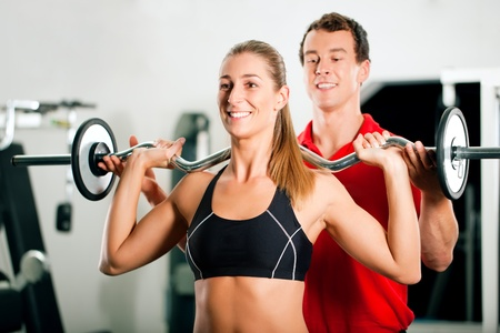 personal trainer: Woman in gym with personal fitness trainer exercising power gymnastics with a barbell Stock Photo