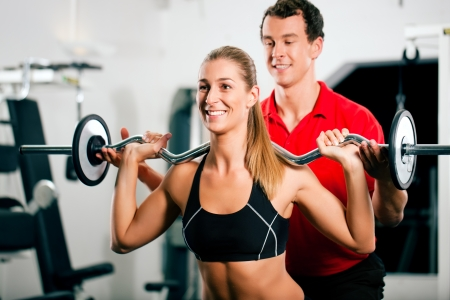 trainer: Woman in gym with personal fitness trainer exercising power gymnastics with a barbell Stock Photo