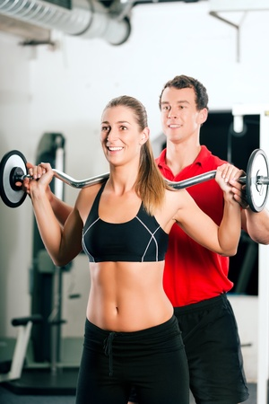 barbell: Woman in gym with personal fitness trainer exercising power gymnastics with a barbell Stock Photo