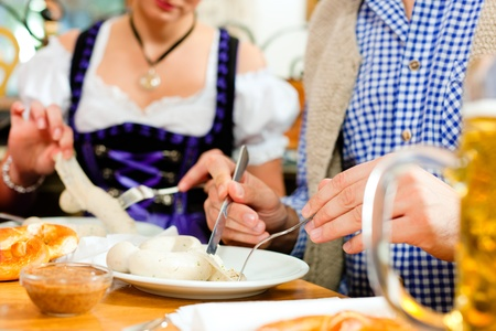 group of young men and women in traditional Bavarian Tracht having a breakfast with white veal sausage, pretzel, and beer Stock Photo - 8295263