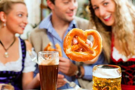 Inn or pub in Bavaria - group of young men and women in traditional Tracht drinking beer and eating pretzel photo