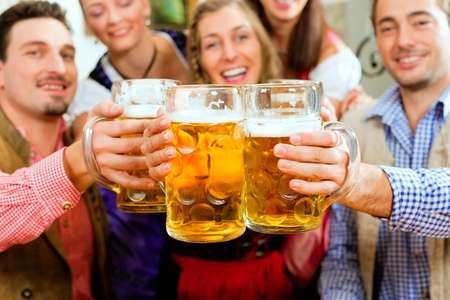 Inn or pub in Bavaria - group of five young men and women in traditional Tracht drinking beer and having a party with beer Stock Photo - 8295266
