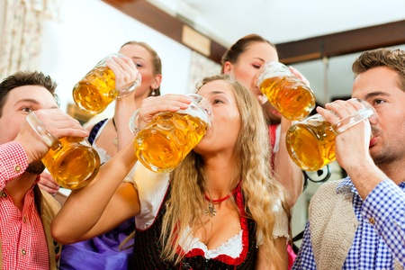 beer drinking: Inn or pub in Bavaria - group of five young men and women in traditional Tracht drinking beer and having a party with beer