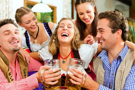 Inn or pub in Bavaria - group of five young men and women in traditional Tracht drinking beer and having a party with beer Stock Photo - 8295294