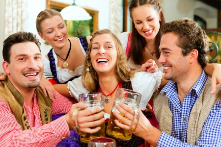 steins: Inn or pub in Bavaria - group of five young men and women in traditional Tracht drinking beer and having a party with beer