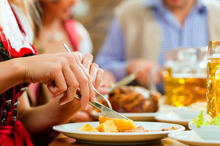 an inn: Inn or pub in Bavaria - group of young men and women in traditional Tracht drinking beer and eating roast pork with dumplings