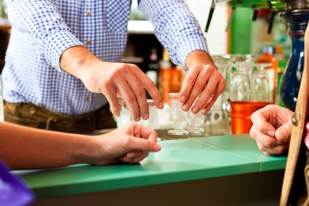 Barkeeper putting hard liquor glasses on bar, people waiting for a drink standing around (just hands) Stock Photo - 8295260