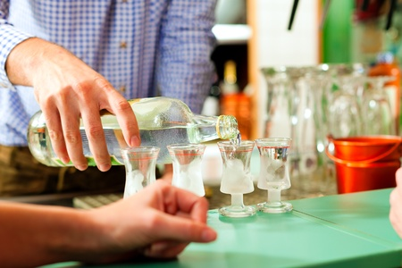 Barkeeper pouring hard liquor into glasses standing on the bar  Stock Photo - 8295256
