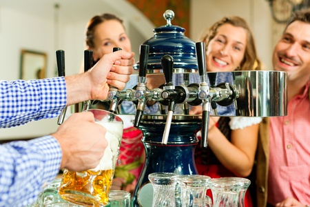 steins: Man drawing a beer from tap on a kegerator in pub or inn, people in Bavarian Tracht are standing in the background Stock Photo