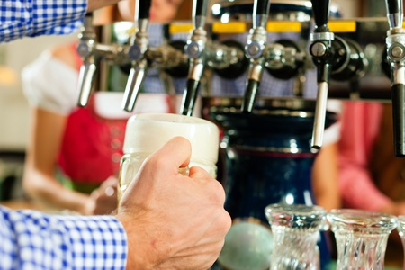 beer tap: Man drawing a beer from tap on a kegerator in pub or inn, people in Bavarian Tracht are standing in the background Stock Photo