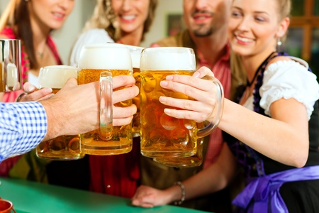 Inn or pub in Bavaria - group of young men and women in traditional Tracht having a party with beer, the steins are standing on the bar Stock Photo - 8295279