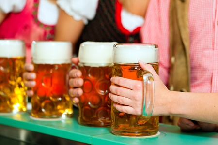 tracht: Inn or pub in Bavaria - group of young men and women in traditional Tracht having a party with beer, the steins are standing on the bar
