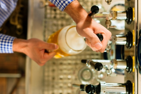 beer glass: Man drawing a beer from tap on a kegerator in pub or inn