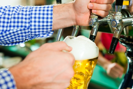Man drawing a beer from tap on a kegerator in pub or inn photo