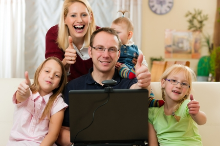 Family in front of computer having video conference photo