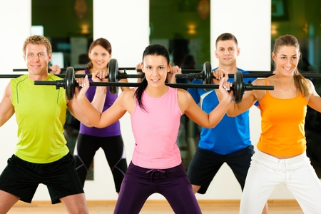 training group: Fitness group with barbell in gym