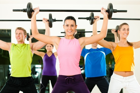 barbell: Fitness group with barbell in gym