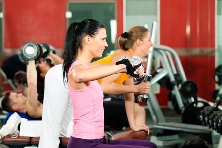 krachtige vrouw: Mensen in sportschool oefenen met gewichten