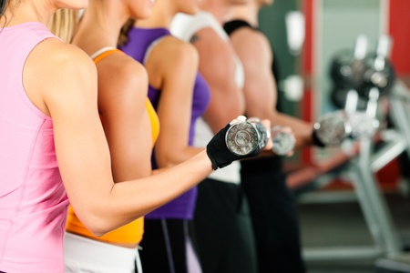 People in gym exercising with dumbbells Stock Photo - 9415548