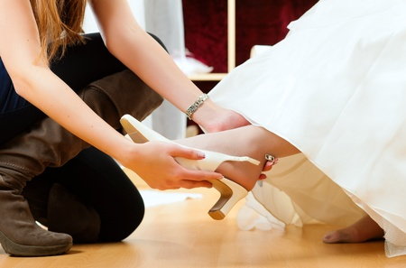 Bride at the clothes shop for wedding dresses; she is choosing a dress is fitting bridal shoes photo