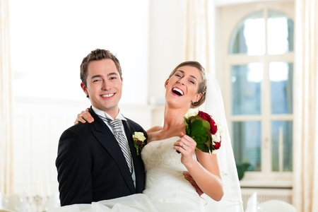 butonniere: Bridal couple - groom is carrying his bride Stock Photo