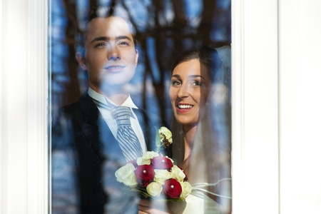 Bridal couple standing at the window at their wedding and looking outside photo