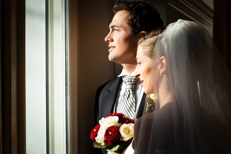 butonniere: Bridal couple standing at the window at their wedding and looking outside Stock Photo