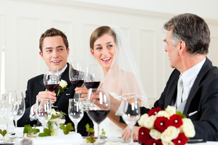 Wedding party at dinner - Bridal couple with father of bride photo