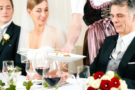 guests: Wedding party at dinner - the dish is going to be served Stock Photo