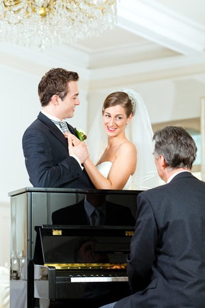 Bridal couple in front of a piano, the pianist is playing a waltz photo
