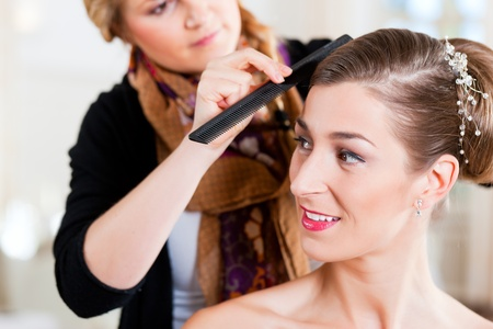 Stylist pinning up a brides hairstyle before the wedding photo