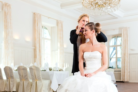 bridal gown: Stylist pinning up a brides hairstyle before the wedding Stock Photo