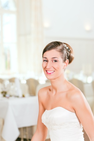 Smiling bride with swept-back hair before the wedding photo