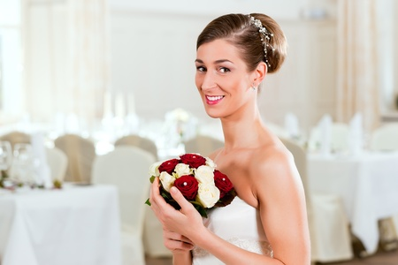 chignon: Bride with bridal bouquet in a hall at the wedding day