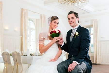 lustre: Bridal couple waiting for ceremony in a decorated hall Stock Photo
