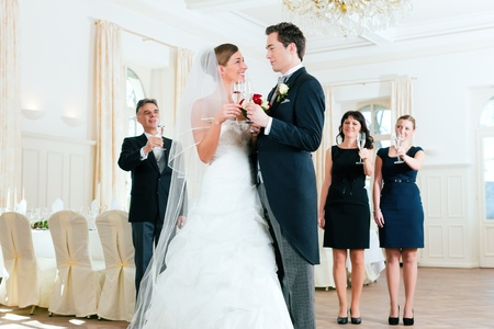 wedding party: Bridal couple clinking glasses while the guests standing in the background