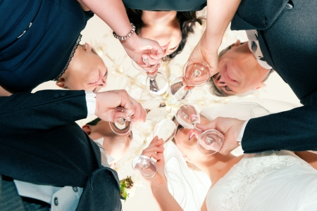 Wedding party bride, groom and bride father clinking glasses with sparkling wine standing under a luster - close-up photo