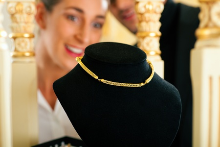 Woman at the jeweller is looking for jewellery photo