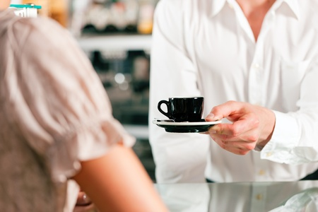 Coffeeshop - barista in cafe waits a coffee to a client photo