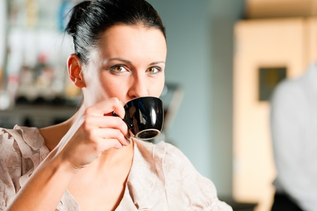 vivre: Woman in a coffeeshop or cafe enjoys her cappuccino