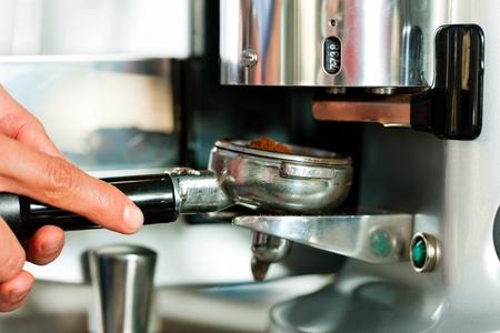 barista: Barista prepares espresso in his coffeeshop; close-up Stock Photo