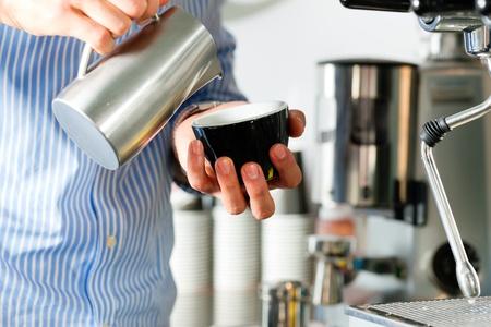 Barista prepares cappuccino in his coffeeshop; close-up photo