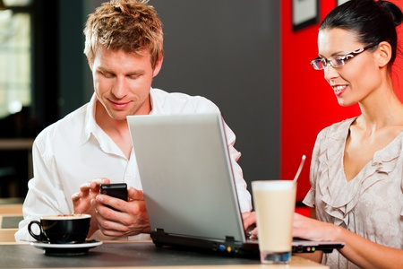 Couple in coffeeshop with laptop and mobile; obviously they are working photo